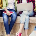 キャンパスのベンチに座る学生