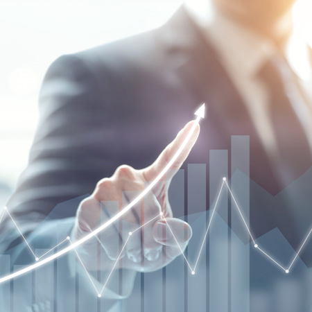 A person in a suit drawing an upward trending curve on a line chart