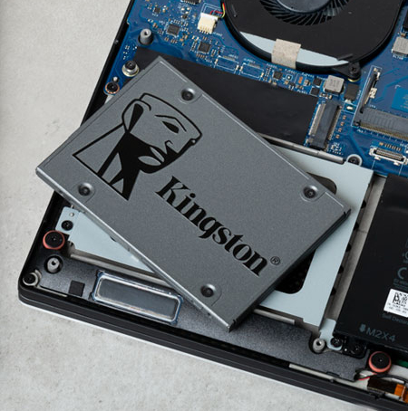 SSD storage drive on top of a disassembled laptop PC