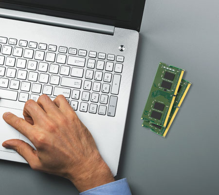 Two RAM modules next person's hand on a laptop