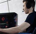 책상 앞에서 게임용 의자에 앉아 데스크톱 PC로 온라인 비디오 게임을 즐기고 있는 젊은 남성