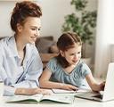 自宅でテーブル上のノートパソコンの前に座り、娘の宿題のオンライン検索を手伝う女性