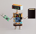 miniature DIY robot holding a USB flash drive board and an SD memory card