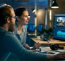 ein Mann und eine Frau in einem Büro, die ein Video auf 2 Monitoren bearbeiten