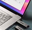 DataTraveler Max USB ドライブ 2 台のうち 1 台がノートパソコンに挿入され、もう 1 台がそばのデスクの上にある様子