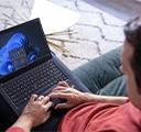 seorang pria di depan laptopnya di rumah sedang menyesuaikan layar mulai Windows 11 baru