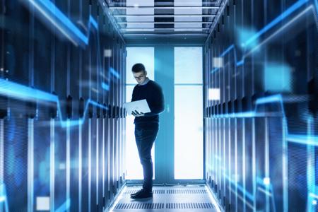 Immagine di un uomo che tiene in mano un laptop in una sala server con una serie di simboliche connessioni fluorescenti a rappresentare connessioni di rete