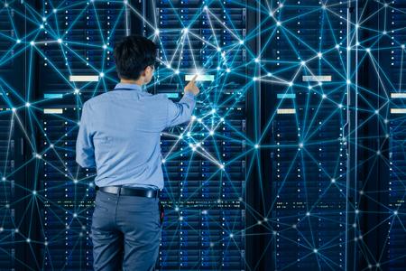 Uomo che preme un pulsante su un server, circondato da una serie di simboli raffiguranti linee di connessioni di rete.