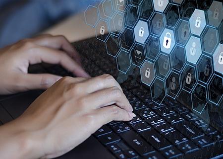 Ręce piszące na laptopie z grafiką przedstawiającą kłódki unoszące się przed ekranem