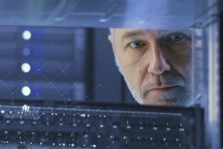 Mann schaut durch den Raum in einen Serverschrank