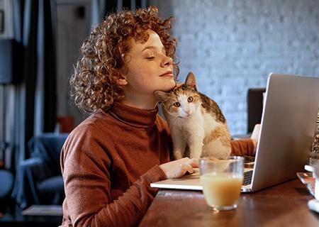 Kobieta pracująca w domu na laptopie w towarzystwie kota na biurku