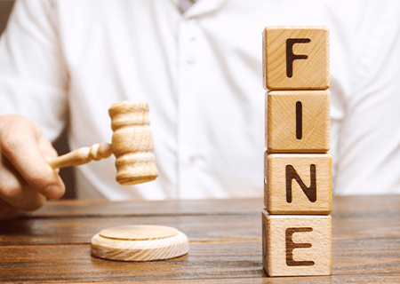 close up view of wooden blocks with the word FINE and a gavel