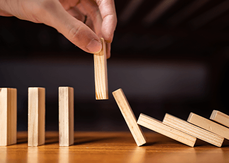 a hand pulling one domino piece stopping falling ones from collapsing the rest