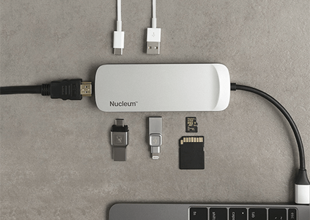 a close-up image of the Nucleum hub plugged in a laptop on a desk with USBs and cards for different ports