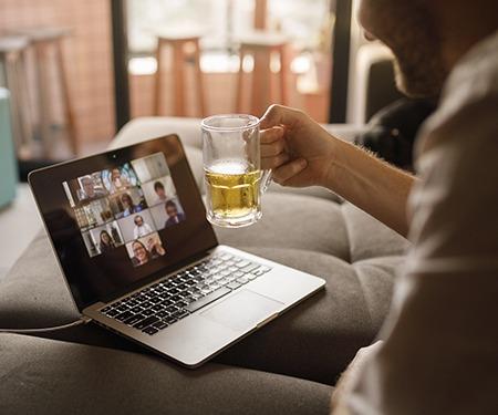 Użytkownik laptopa w wideoczacie, z piwem w ręku