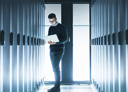 Man standing near server racks with a laptop PC