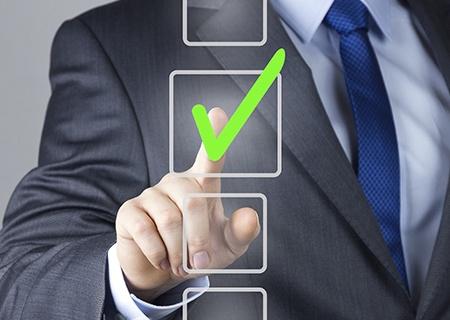 Mężczyzna ręką wskazuje na jeden z kwadratów na ilustracji z zielonym symbolem zaznaczenia