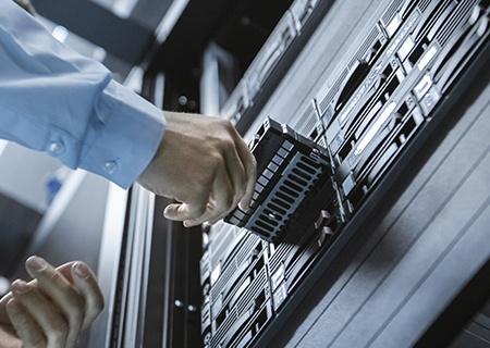 Inżynier IT instalujący dysk w szafie serwerowej