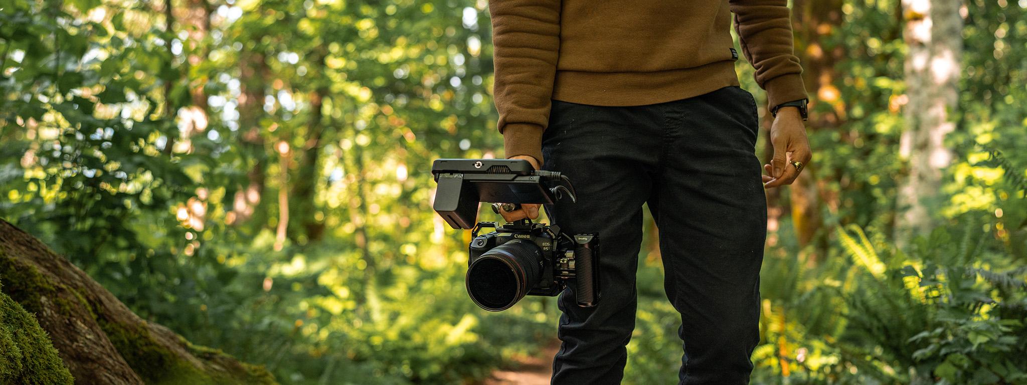 Ben sosteniendo una cámara Canon EOS R5 con un trípode en un área boscosa.