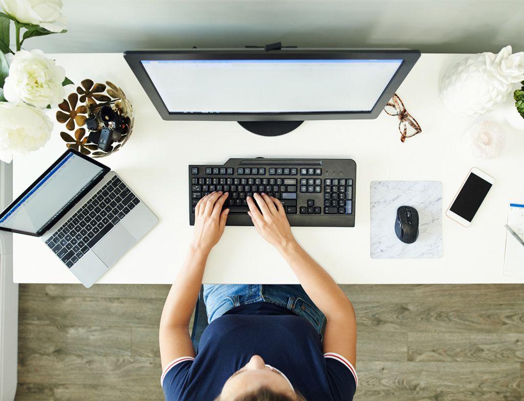 Вид сверху на руки человека, работающего на клавиатуре на компьютерном столе, рядом с монитором, ноутбуком, мышью и мобильным телефоном