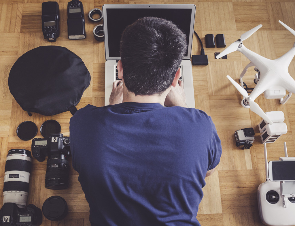 A man using a laptop in the floor with a drone, DSLR, and action cam nearby