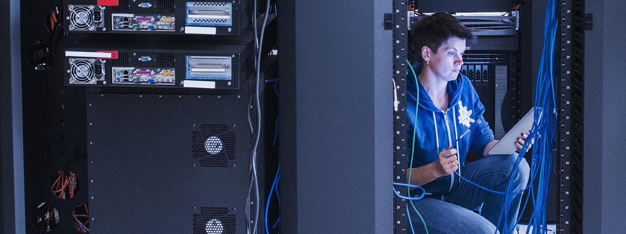 Un tecnico di rete donna vicino a un server rack con un cavo ethernet