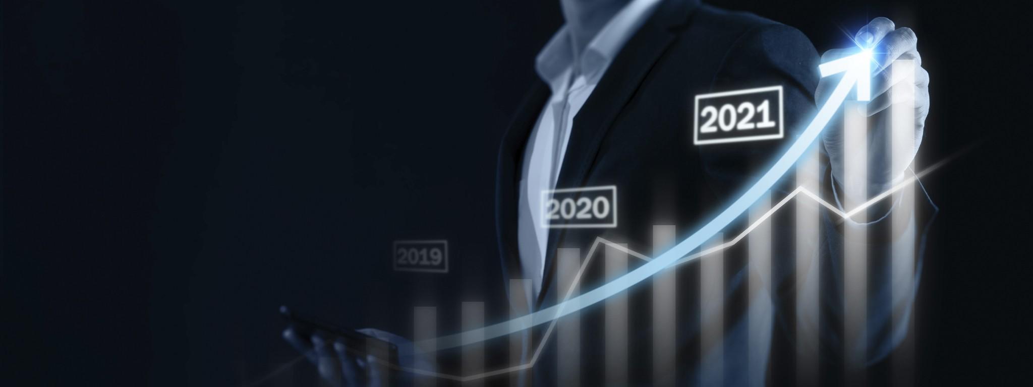 Бизнесмен указывает на иллюстрацию с графиком роста рынка за несколько лет вплоть до 2021 года