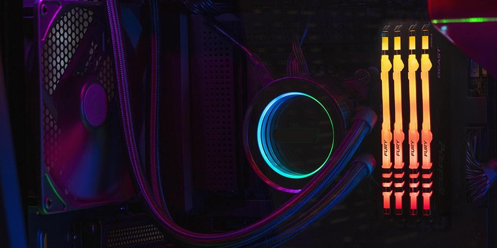Kingston FURY Beast RGB mit einem CPU-Lüfter und in einem Motherboard eingesteckten Kabeln, mit Monitor auf der linken Seite mit den PC-Spezifikationen