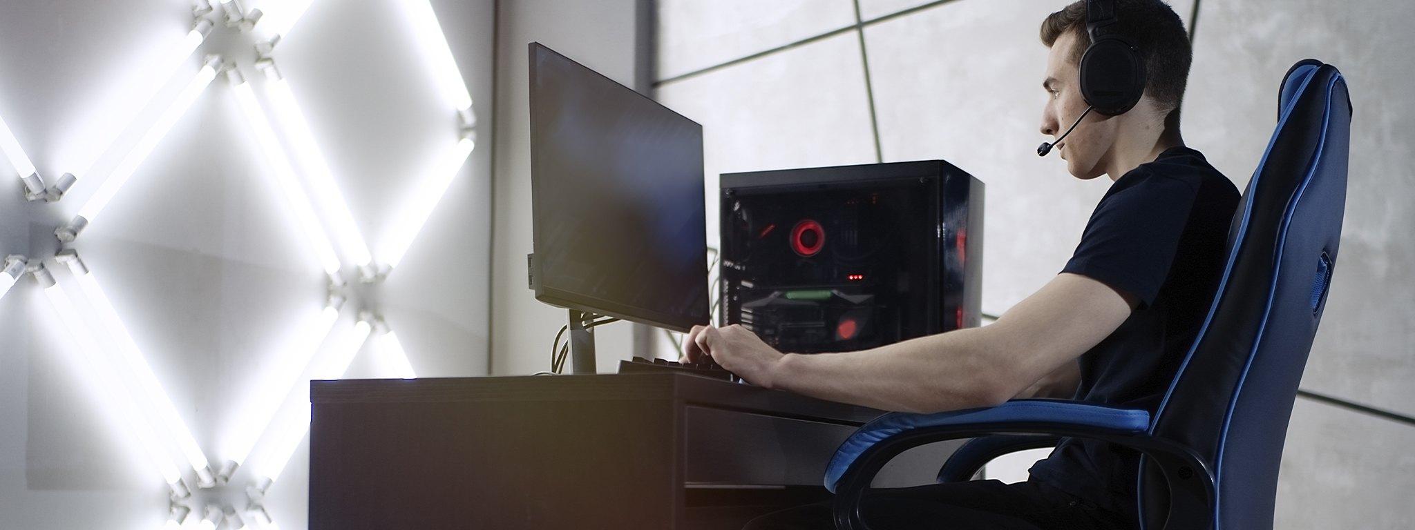 Młody mężczyzna siedzący na fotelu gamingowym przy biurku i grający w grę na komputerze stacjonarnym