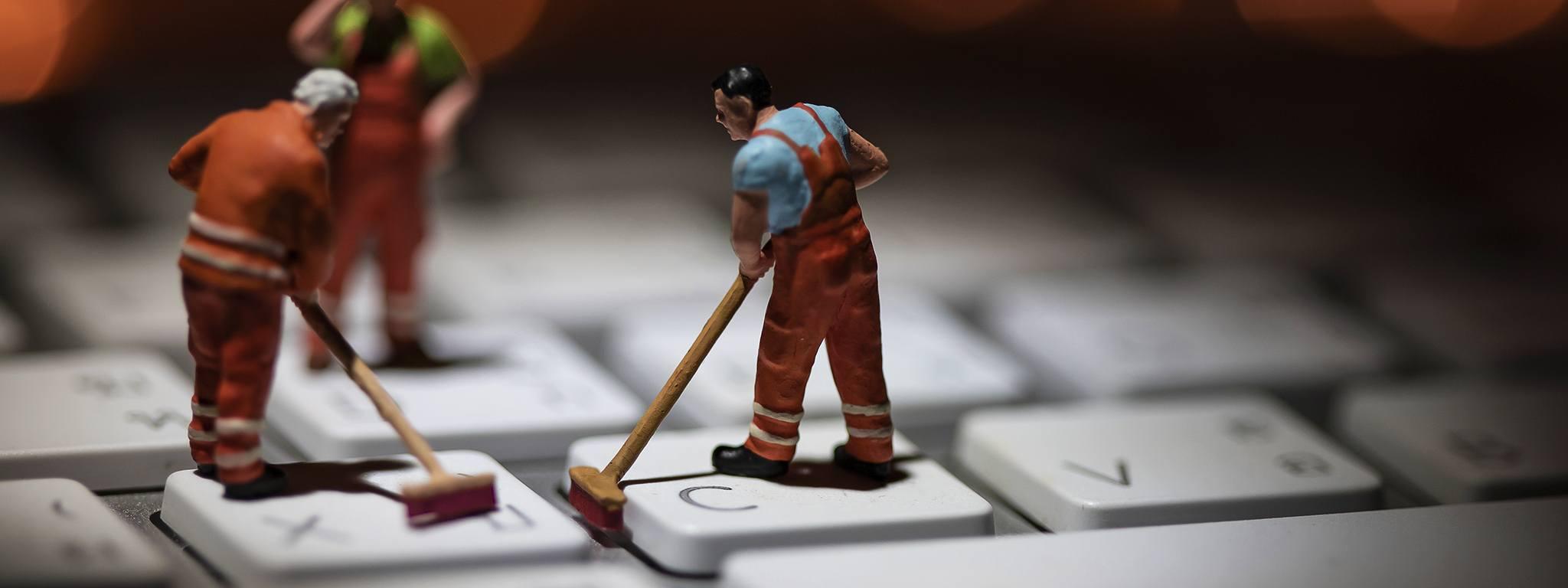 Mini-personnes nettoyant un clavier blanc avec lampes clignotantes orange en arrière-plan