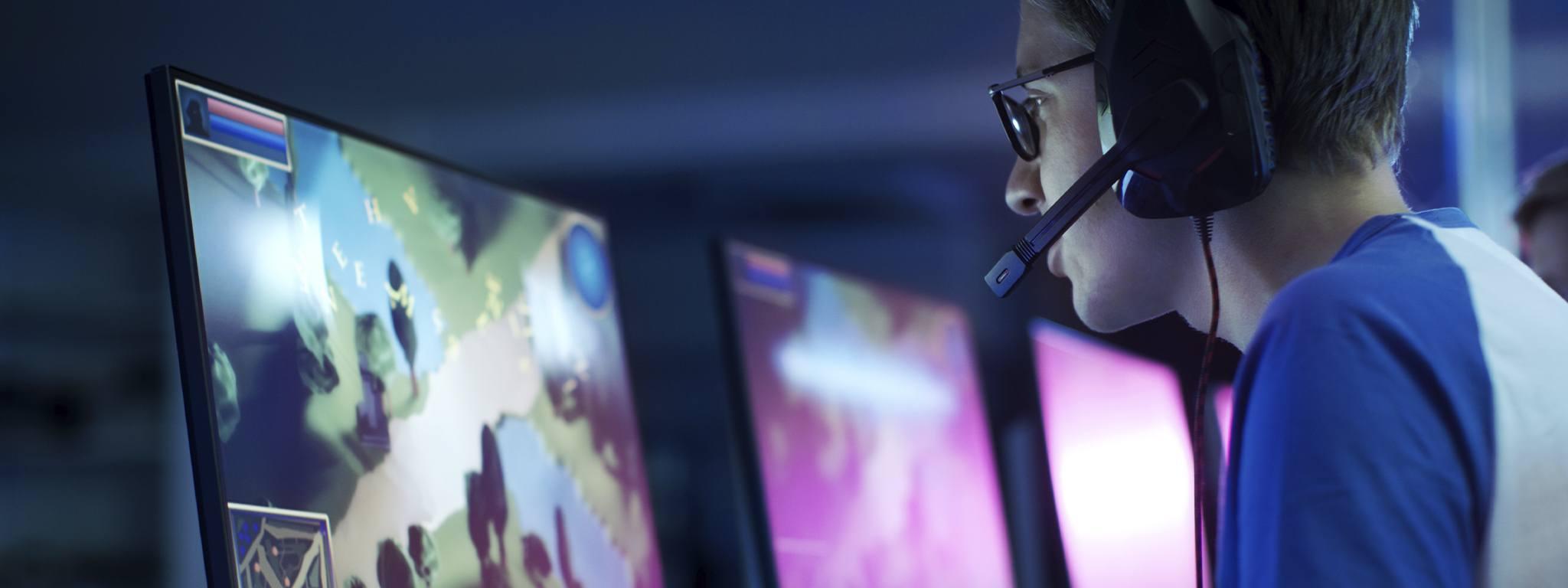 Gracz e-sportowy grający i transmitujący swoją rozgrywkę na komputerze