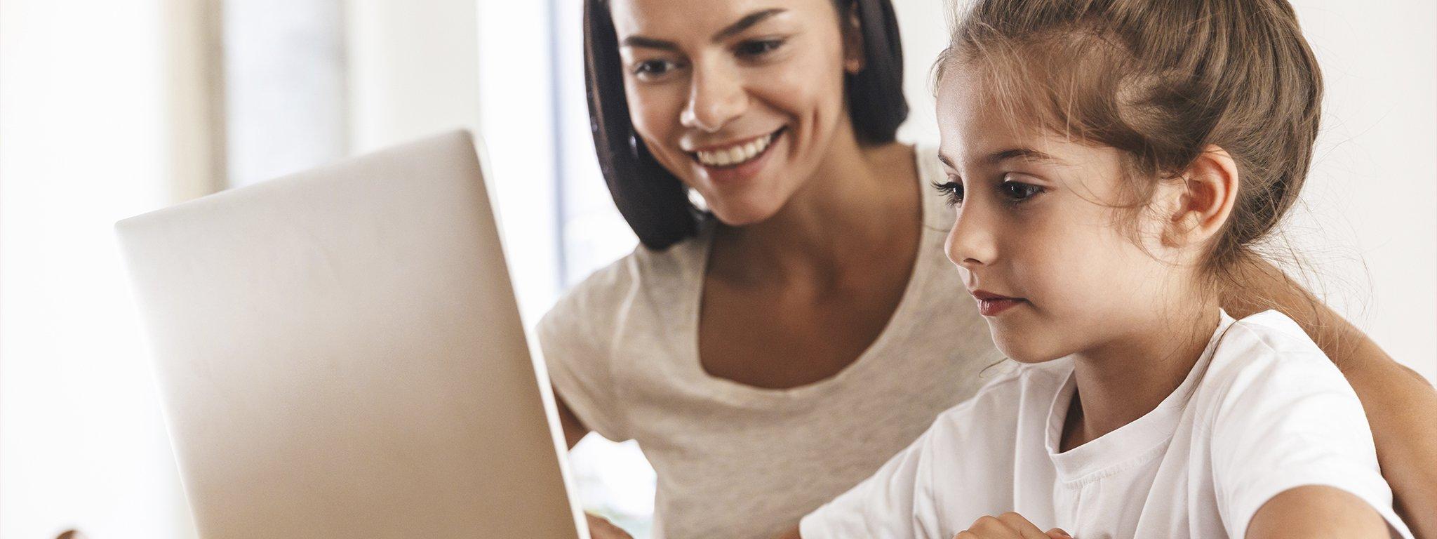 bir anne ve kızı evde bir dizüstü bilgisayar kullanırken bir masada gülümseyerek oturuyor