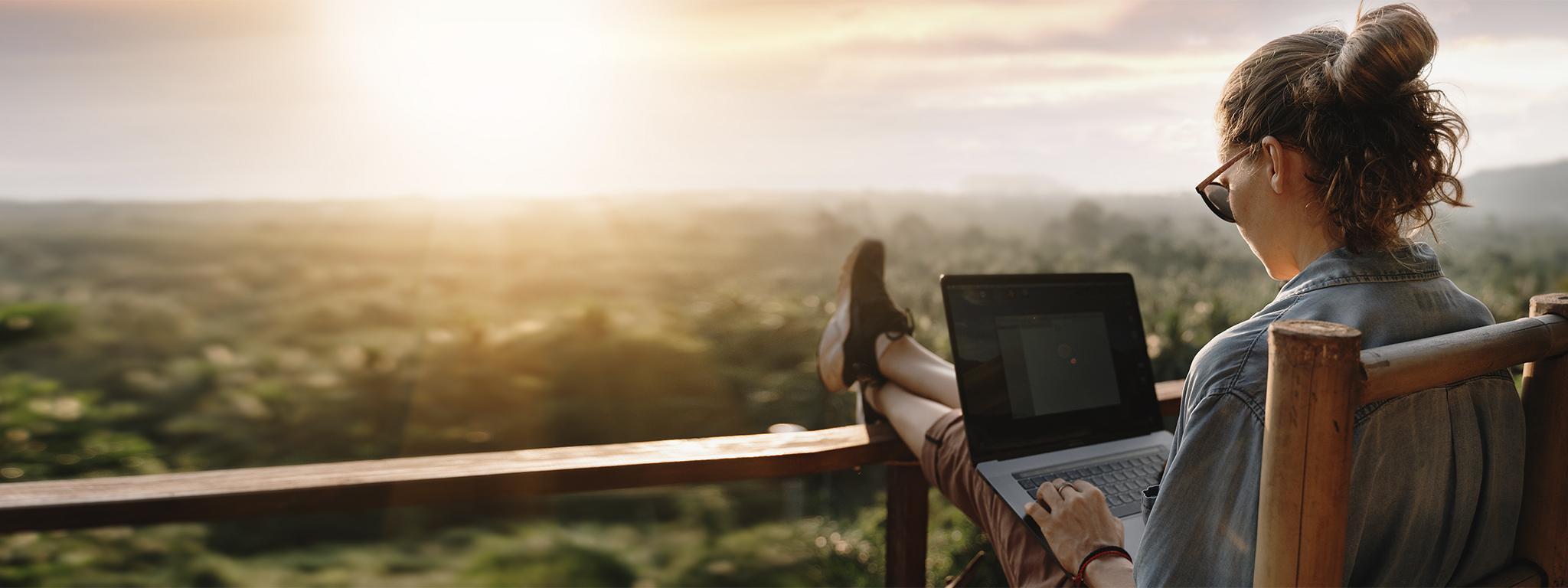 una joven trabajando con un portátil en un balcón al atardecer