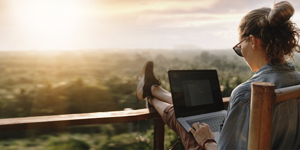 a girl working on a laptop in the sunset on the balcony