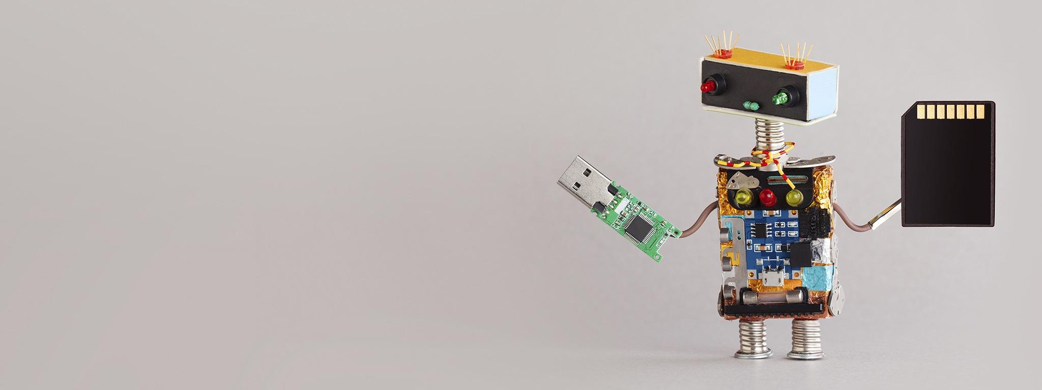 robot en miniatura sosteniendo una unidad Flash USB y una tarjeta de memoria SD
