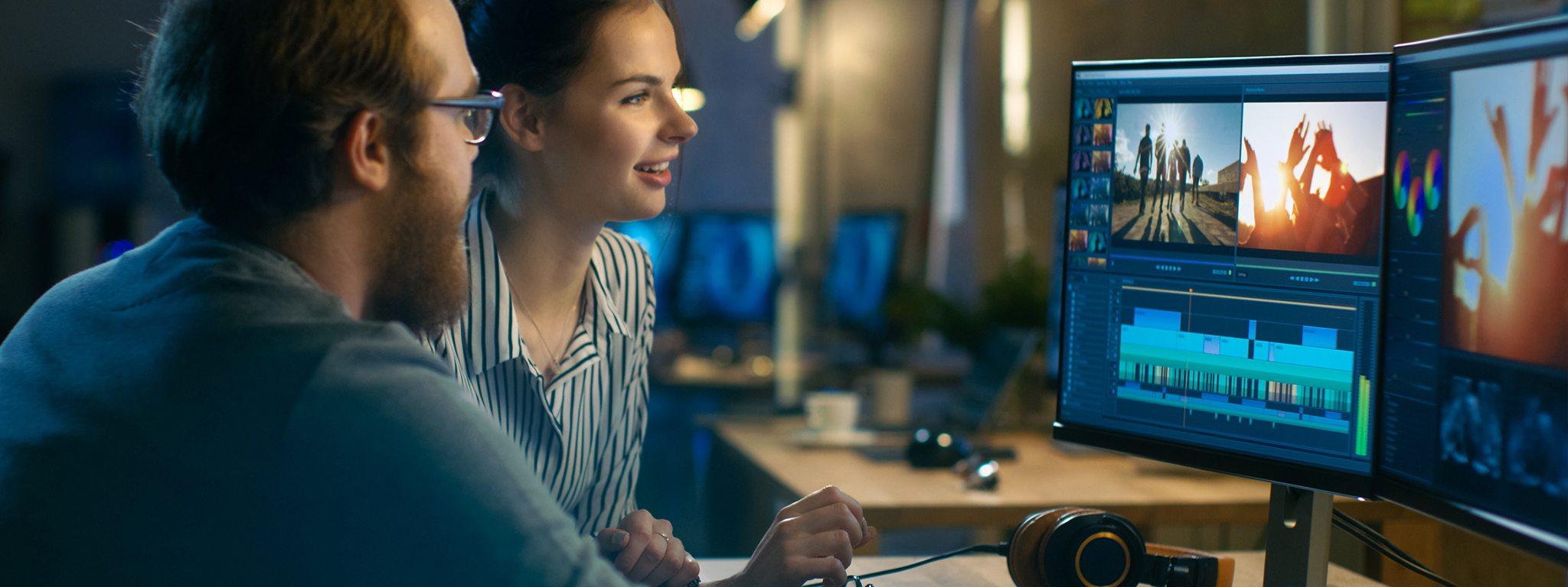 một người đàn ông và một người phụ nữ trong văn phòng đang chỉnh sửa video trên 2 màn hình