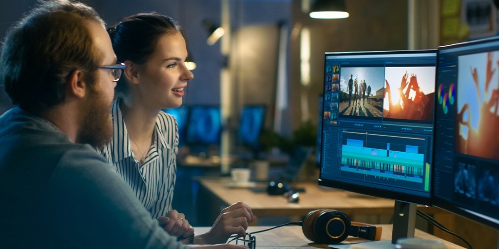 a man and a woman in an office editing a video on 2 monitors