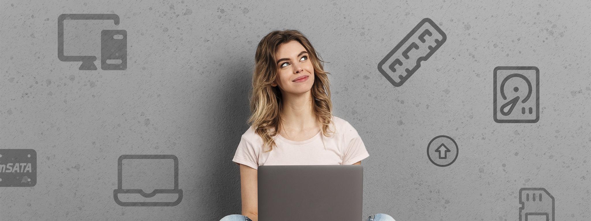 một người phụ nữ ngồi trên sàn nhà đang dùng máy tính xách tay và nhìn các biểu tượng phần cứng máy tính khác nhau được minh họa trên tường