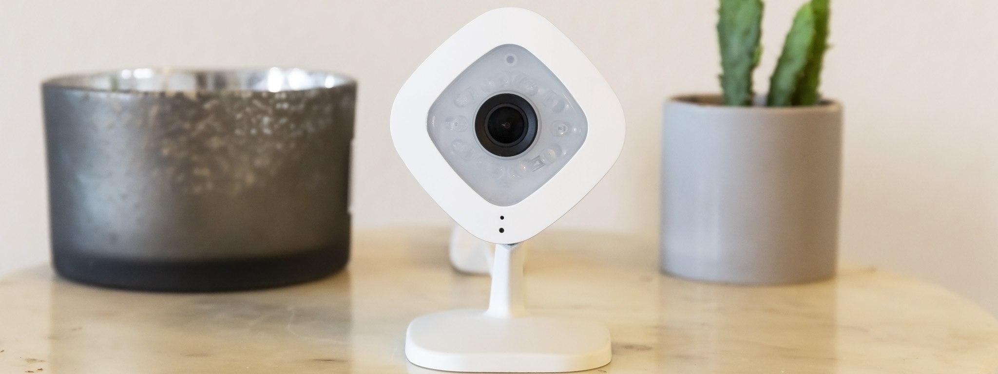 Immagine di una telecamera di sicurezza posizionata tra un porta candela e un cactus in vaso.