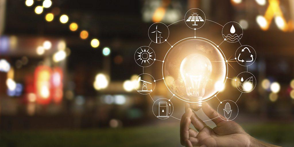 Eine Hand, die eine Glühbirne vor einer Weltkugel hält, illustriert mit verschiedenen Energiequellen-Symbolen