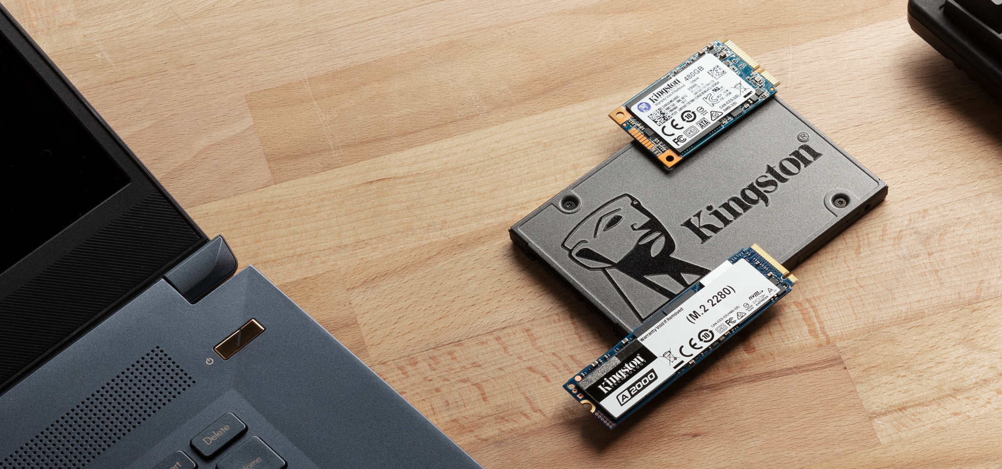 SATA ve M.2 SSD'ler masada bir dizüstü bilgisayarın yanında duruyor.