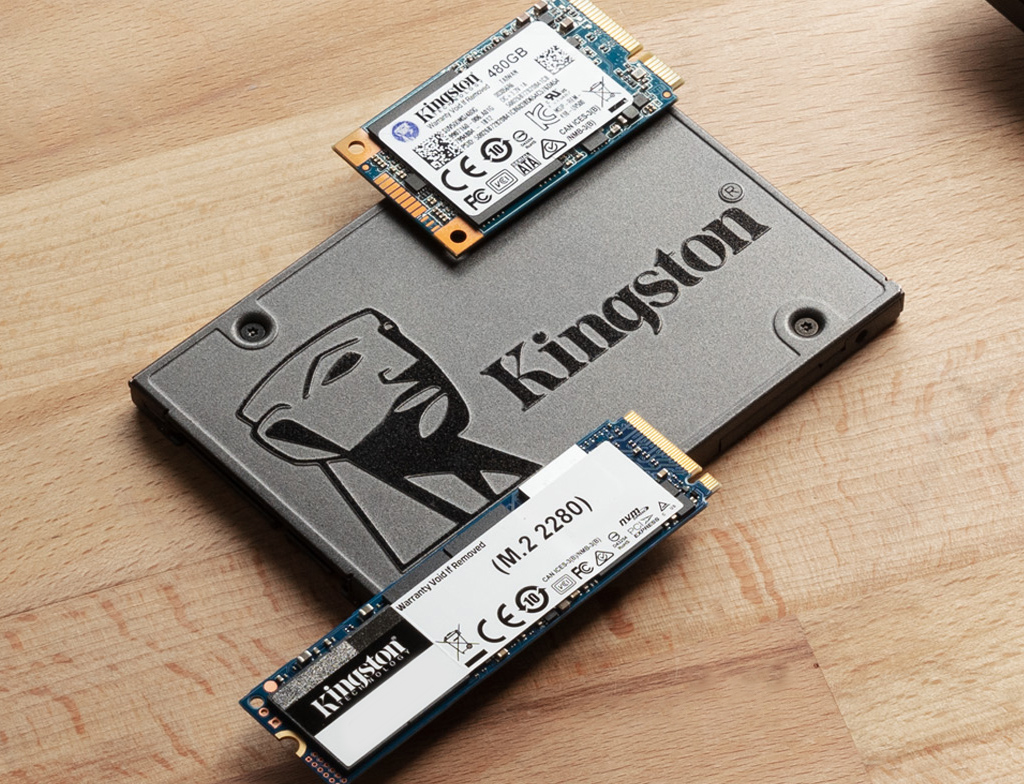 SATA and M.2 SSDs sitting on a table next to a laptop