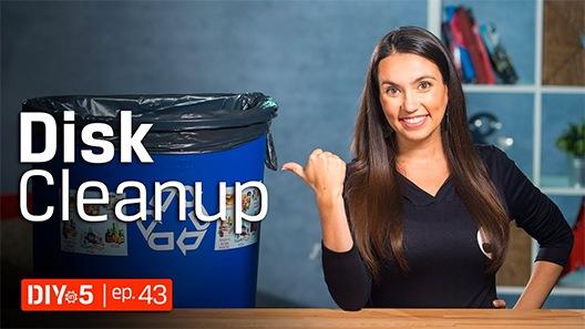 Trisha, bir masanın önünde duruyor ve solundaki bir çöp kutusunu işaret ediyor